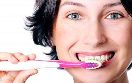 Mulher sorrindo e escovando os dentes - LUZ Loja de Consultoria